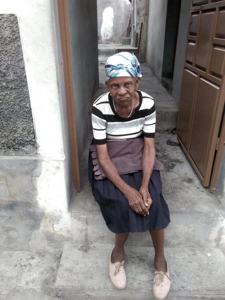 Vecina sentada en a puerta de su casa